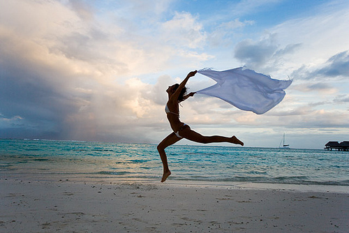 woman with sarong jumping on tropical beach at sunset